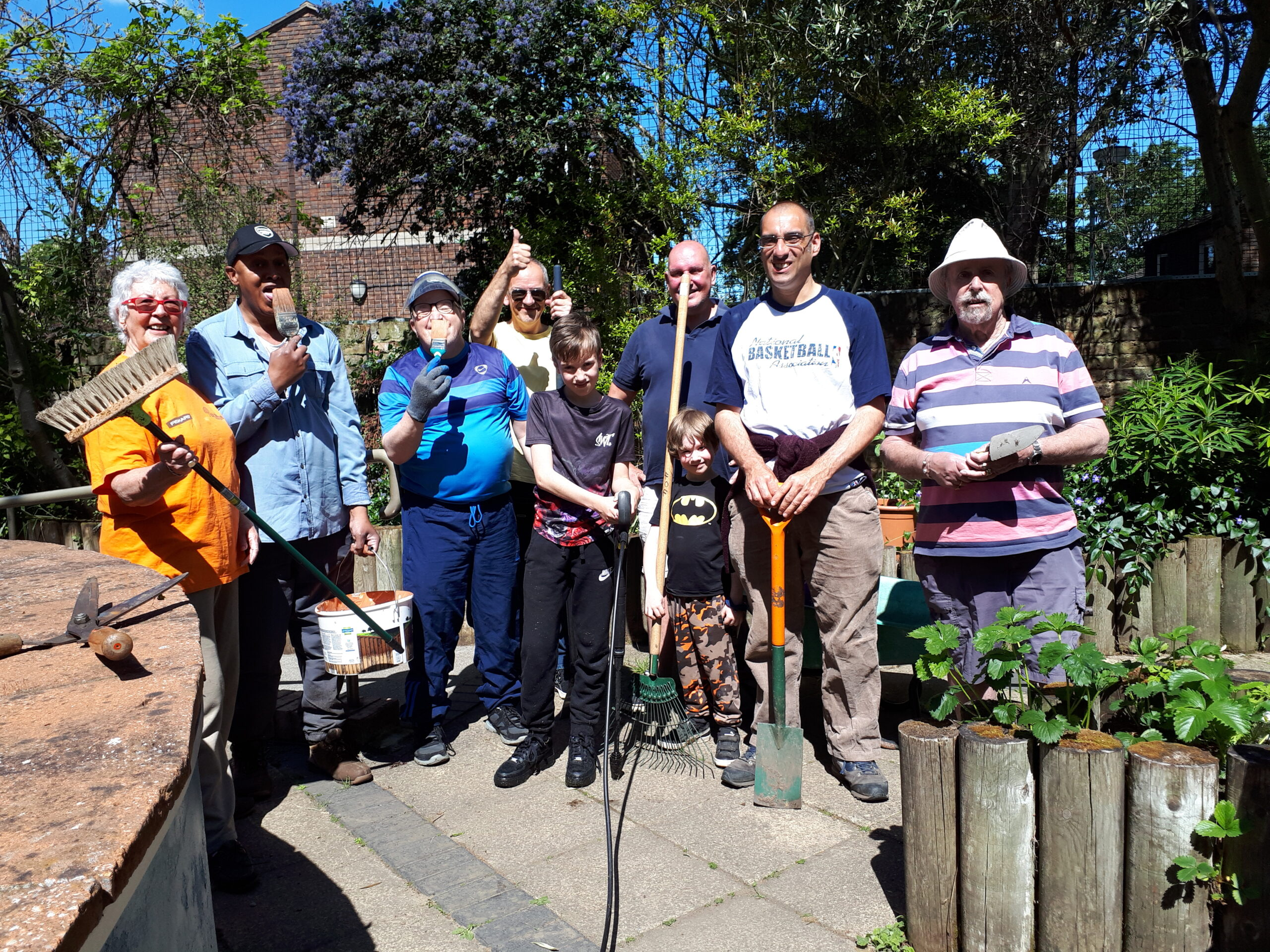 Image shows a group photo of garden volunteers smiling an posing with tools.