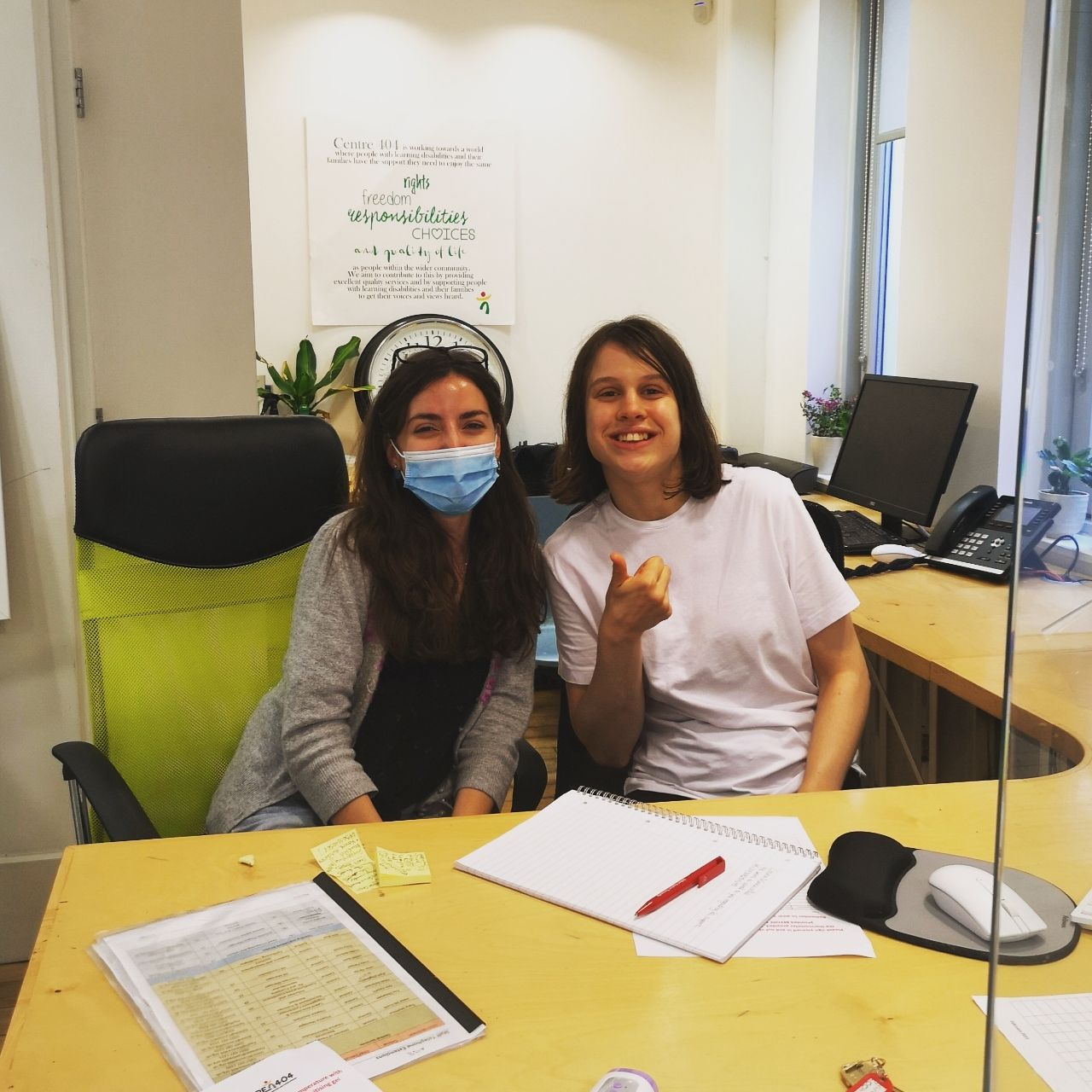 Photo shows our volunteer Judith and our Receptionist Alexa smiling on reception.